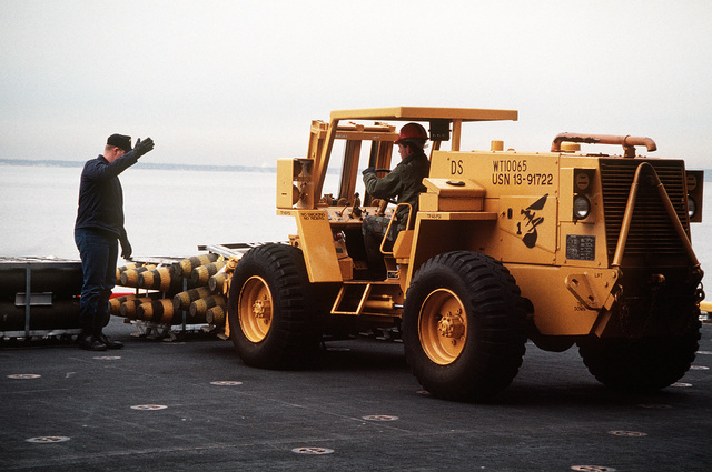 An ordnanceman uses a forklift to move pallets of 500-pound bombs during an ammunition offload from the amphibious assault ship USS WASP (LHD-1)