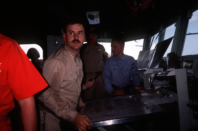 """LT Michael Baumann coordinates damage control efforts from the bridge of the frigate USS CAPODANNO (FF-1093) during a mass conflagration exercise, part of their six-week refresher training course. During the """"mass conflag,"""" crew members simulate saving their ship after it has received massive structural damage"""