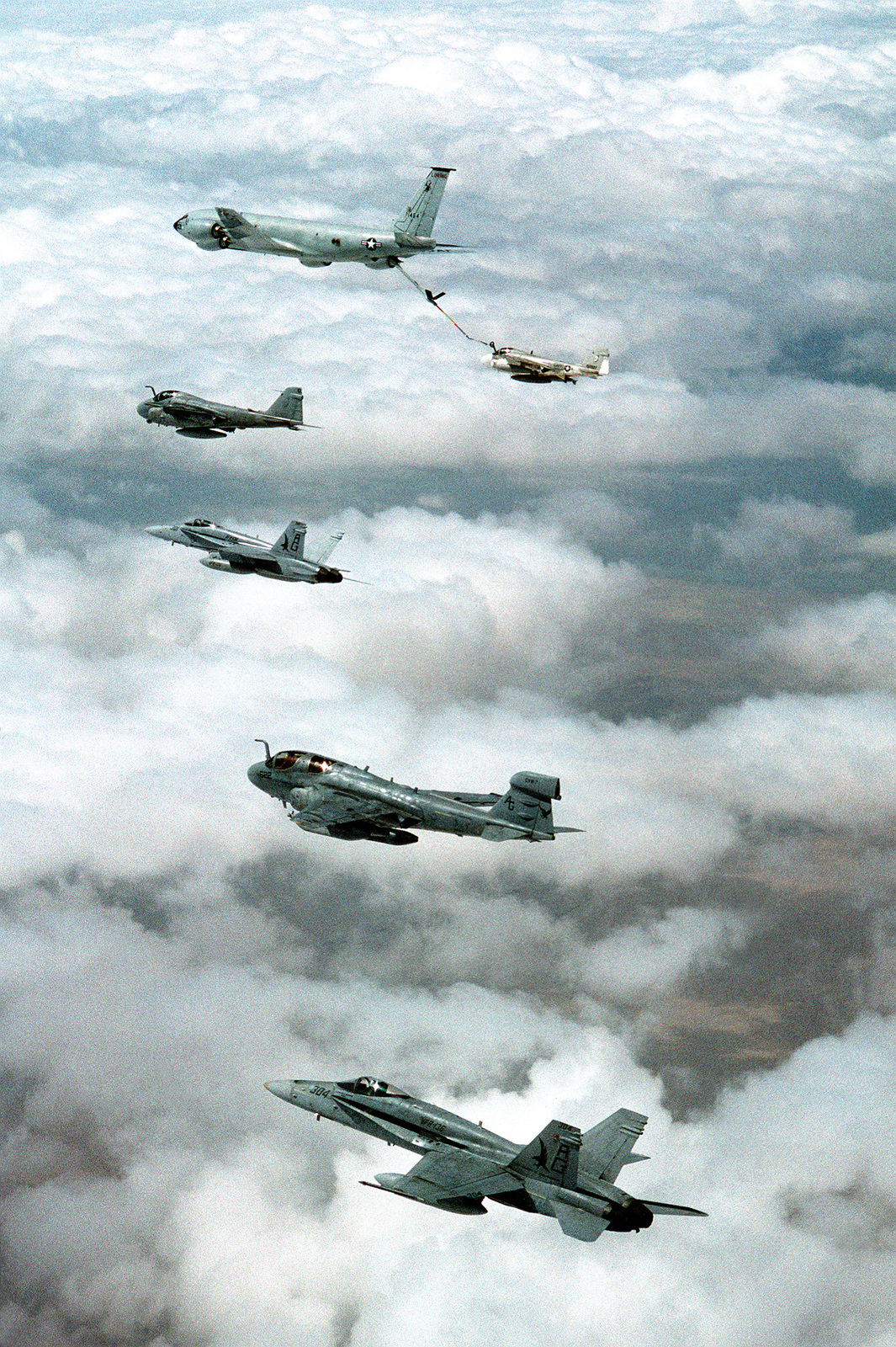 From top to bottom, a U.S. Air Force KC-135R Stratotanker refueling a KA-6D Intruder tanker from Attack Squadron 34 (VA-34), an A-6E Intruder attack aircraft, an F/A-18C Hornet from Strike Fighter Squadron 136 (VFA-136), and an EA-6B Prowler from Tactical Electronic Warfare Squadron 140 (VAQ-140) and another VFA-136 F/A-18C Hornet during flight operations off the nuclear-powered USS DWIGHT D. EISENHOWER (CVN-69) in the Persian Gulf