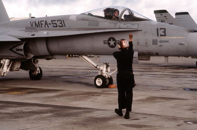 PFC Dwayne Dickey, plane captain, signals to 2LT T. Kehoe, the pilot of a Marine Fighter-Attack Squadron 531 (VMFA-531) F/A-18A Hornet aircraft. Aircraft of the squadron are making their final deployment from Marine Corps Air Station, El Toro, Calif