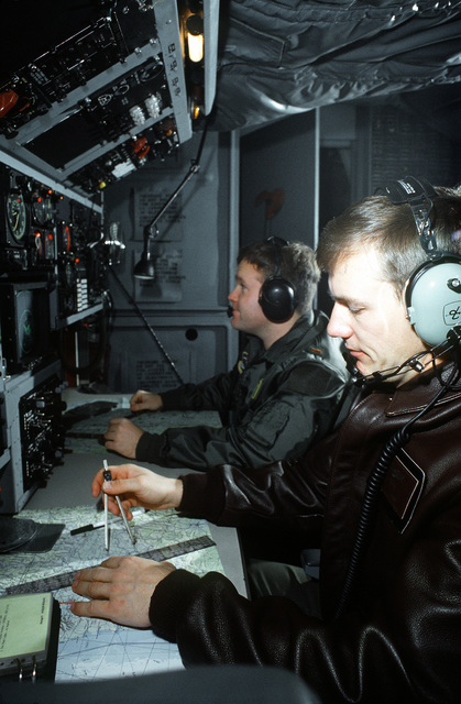 CPT Tim Green (leather coat) and another navigator, 38th Strategic Reconnaissance Squadron, 55th Strategic Reconnaissance Wing, Offutt AFB, preflight their section of an RC-135 Stratolifter aircraft