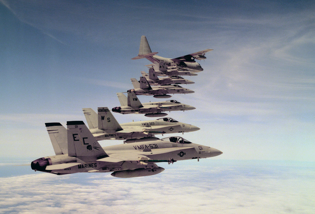 Right side view of Marine Air Group 11 (MAG-11) F/A-18A and F/A-18D Hornet strike fighter aircraft in formation with a Marine Refueling Group 350 (VMGR-350) KC-130 Hercules aircraft over the Marine Corps Air Station
