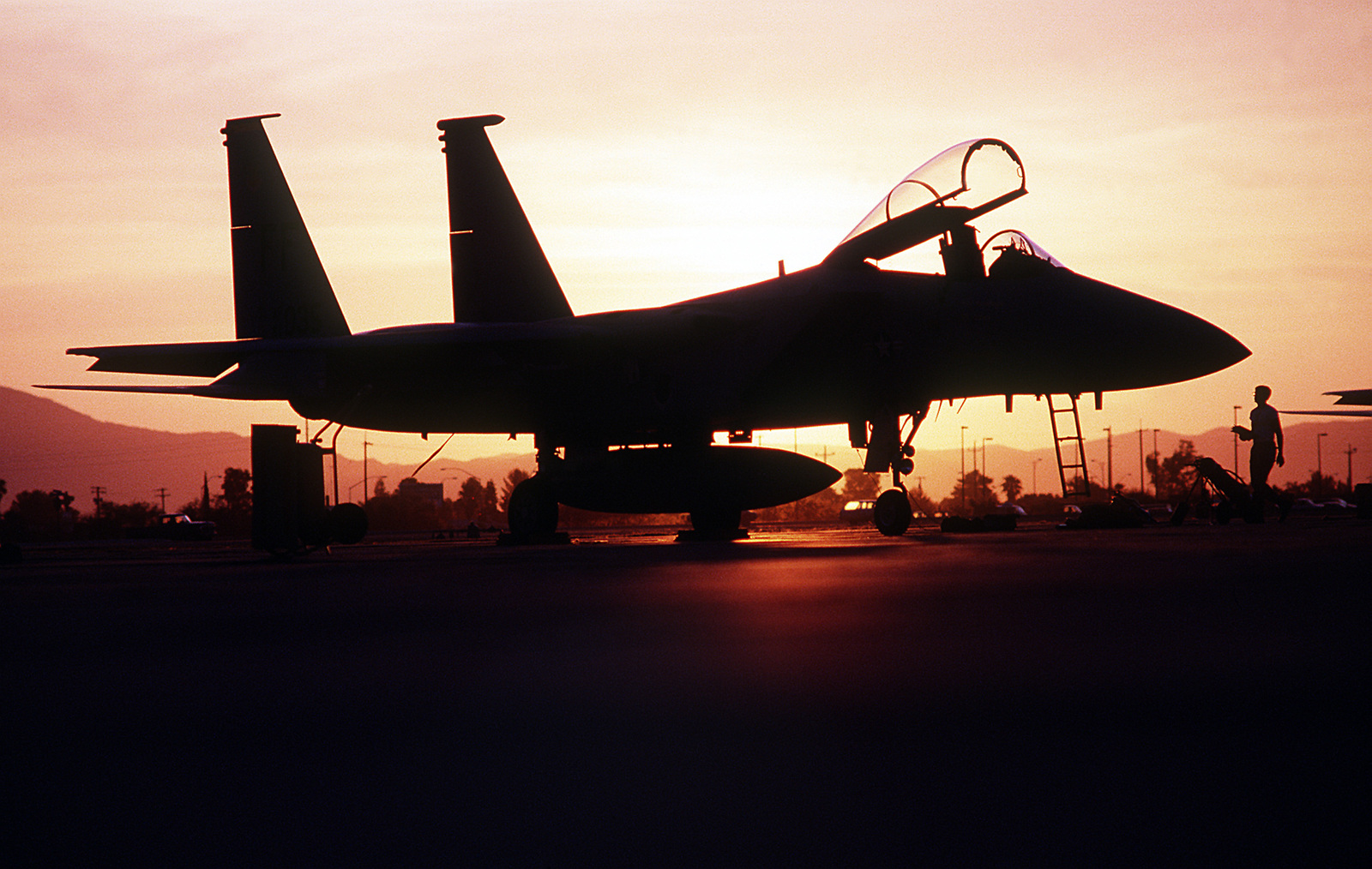 An F-15C Eagle aircraft of the 1ST Tactical Fighter Wing is silhouetted against the sunrise while on a combat patrol near the Iraqi border during Operation Desert Shield