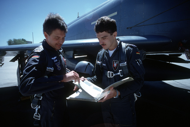 MAJ Reinhard Zyche, left, and CPT Wolfgang Degenmeier, both of the German air force, examine maintenance forms prior to a training mission. The 1ST German Training Squadron uses the base training range complex for initial and advanced F-4E pilot raining. Instructors from the 20th Tactical Fighter Training Squadron (20th TFTS) teach German pilots in the basic F-4 course, RF-4 preparatory training and the fighter weapons instructor course. The 20th TFTS also provides maintenance and operational assistance to the German squadron