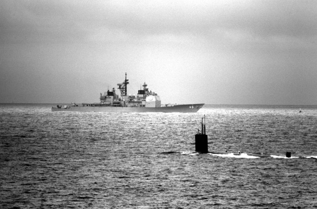 A Sturgeon class nuclear-powered attack submarine is shown deplarting the bay as the guided missile cruiser USS YORKTOWN (CG-48) enters the bay en route to the Norfolk Naval Station