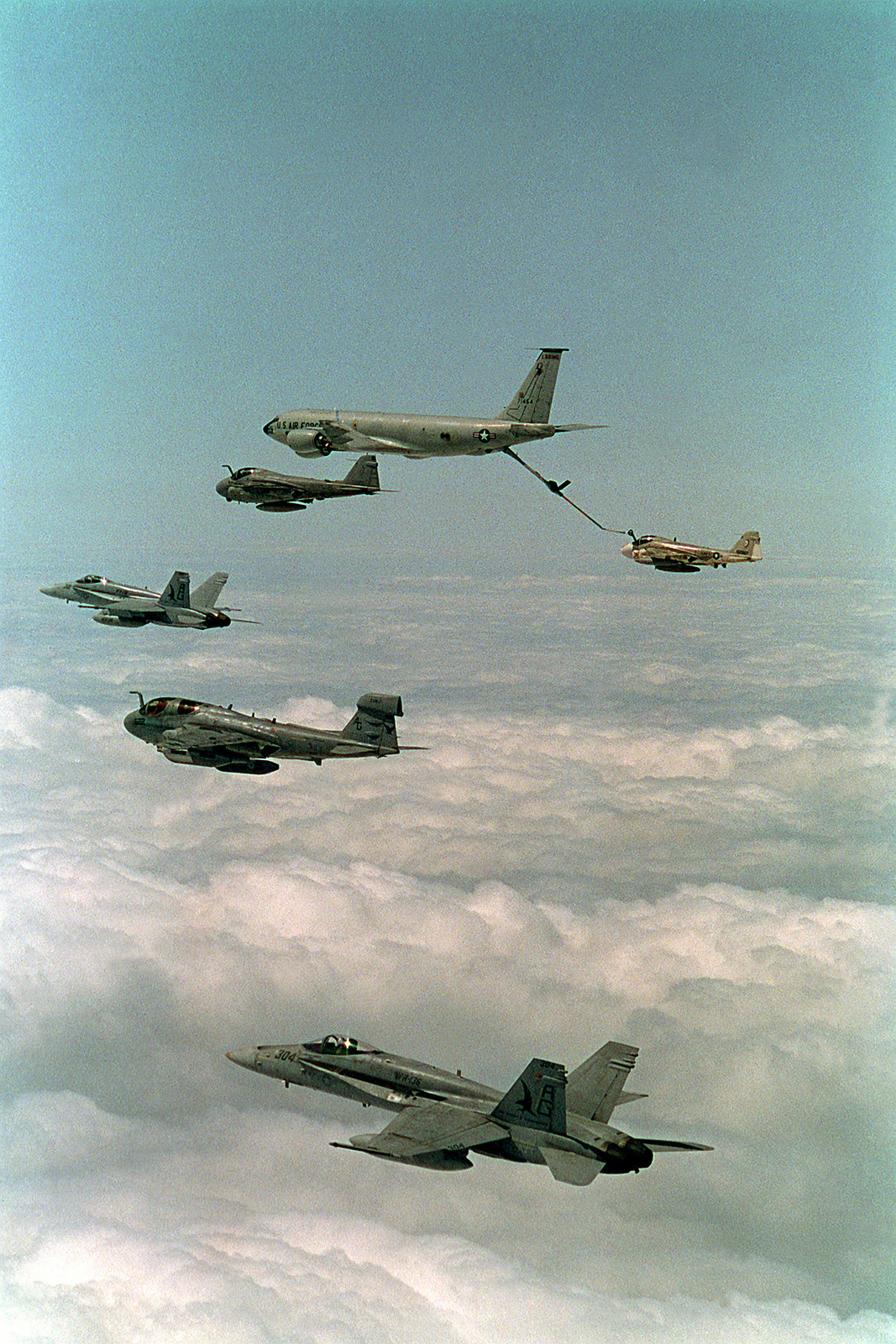 A KC-135D Stratotanker aircraft refuels a KA-6D Intruder aircraft as an A-6E Intruder, a Tactical Electronic Warfare Squadron 140 (VAQ-140) EA-6B Prowler aircraft, and two Strike Fighter Squadron 136 (VFA-136) F/A-18C Hornet aircraft await refueling while flying in formation over the Persian Gulf