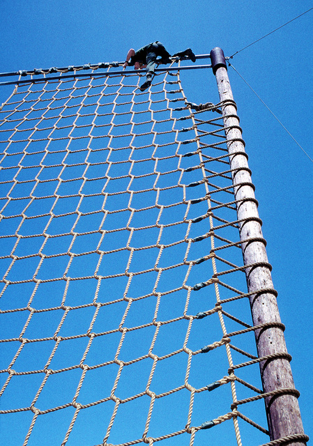 A member of Basic Underwater Demolition/Sea-Air-Land (BUD/S) Class 183 climbs the cargo net on the obstacle course