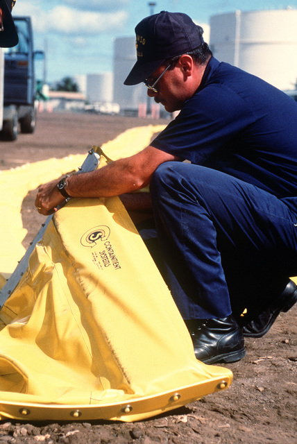 A member of the Coast Guard Marine Safety Office, Honolulu, helps to set up an oil spill containment boom during a training exercise