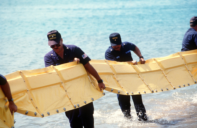 Members of the Coast Guard Marine Safety Office, Honolulu, set up an oil spill containment boom during a training exercise