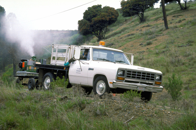 A truck from the Navy Disease Vector Control office sprays an area for mosquitoes