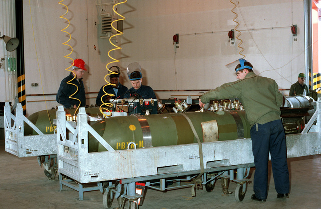 Mineman install firing mechanisms on a Mark 64 Quickstrike mine. Naval Reserve minemen from Mobile Mine Assembly Group (MOMAG) Unit 2622, Seattle, and MOMAG Unit 2016, St. Paul, Minnesota, are training with MOMAG Unit 12 in Japan, building underwater mines in preparation for the Mine Readiness Certification Inspection