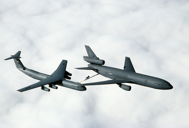 A 79th Air Refueling Squadron (79th AREFS) KC-10A Extender aircraft refuels a 7th Airlift Squadron (7th AS) C-141B Starlifter aircraft as the two planes fly above the clouds over northern California