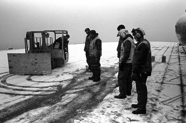 Members of the deck force of the amphibious assault ship USS GUADALCANAL (LPH-7) convert a fork lift truck into a snow plow by placing plywood across skids. The USS GUADALCANAL is in the Blatic taking part in Exercise Teamwork '92