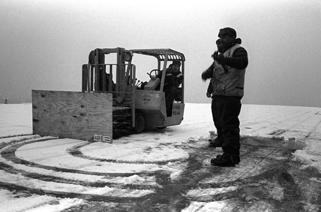Members of the deck force of the amphibious assault ship USS GUADALCANAL (LPH-7) convert a fork lift truck into a snow plow by placing plywood across skids. The USS GUADALCANAL is in the Baltic taking part in Exercise Teamwork '92