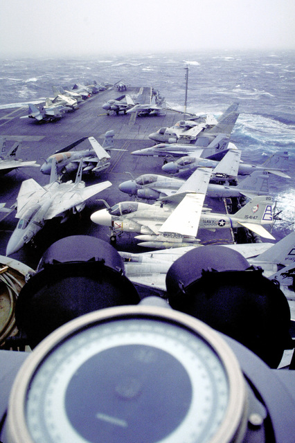 A view of the flight deck of the nuclear-powered aircraft carrier USS DWIGHT D. EISENHOWER (CVN-69) off the coast of Norway during Teamwork '92, a multinational NATO exercise involving 11 nations. Flight deck aircraft include, clockwise from deck center, an EA-6B Prowler electronic warfare aircraft, two F-14A Tomcat fighter aircraft from Fighter Squadron 143 (VF-143), a KA-6D Intruder tanker and two A-6E Intruder aircraft, an F/A-18C Hornet strike-fighter aircraft, and two S-3 Viking anti-submarine aircraft