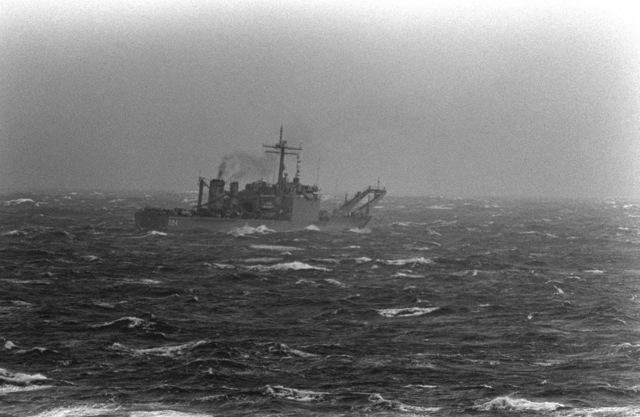 A starboard quarter view of the tank landing ship USS LAMOURE COUNTY (LST-1194) sailing through fog shrouded rough seas. The photograph clearly illustrates the difficult conditions under whIch forces in the Baltic have to operate a great time of the year. The vessel is taking part in NATO Exercise Teamwork '92