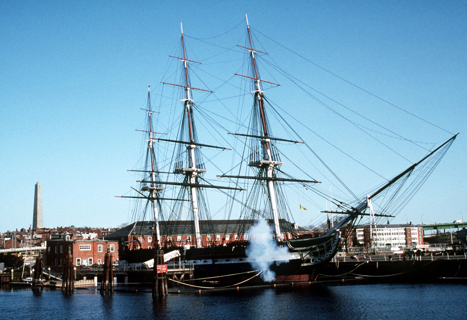 The sail frigate USS CONSTITUTION, the Navy's oldest commissioned warship, fires a single cannon as the U.S. flag is raised at morning colors. In the background, left, is the Bunker Hill monument