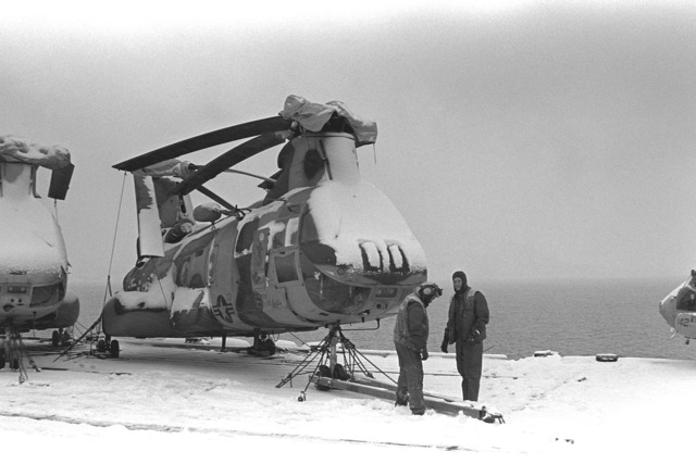 Flight deck personnel attach a tow bar to the front of a CH-46E Sea Knight helicopter of Marine Medium Helicopter Squadron 263 (HMM-263) on board the amphibious assault ship USS GUADALCANAL (LPH-7) during NATO Exercise Teamwork '92