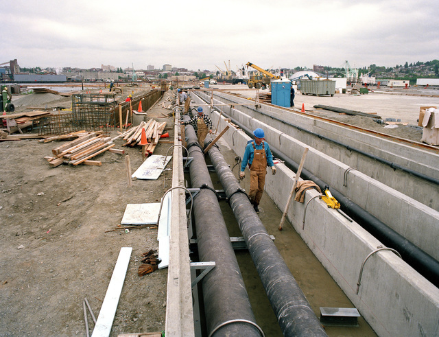 Construction crews check pipe and foundations during construction of Naval Station Everett, the future home of a carrier battle group