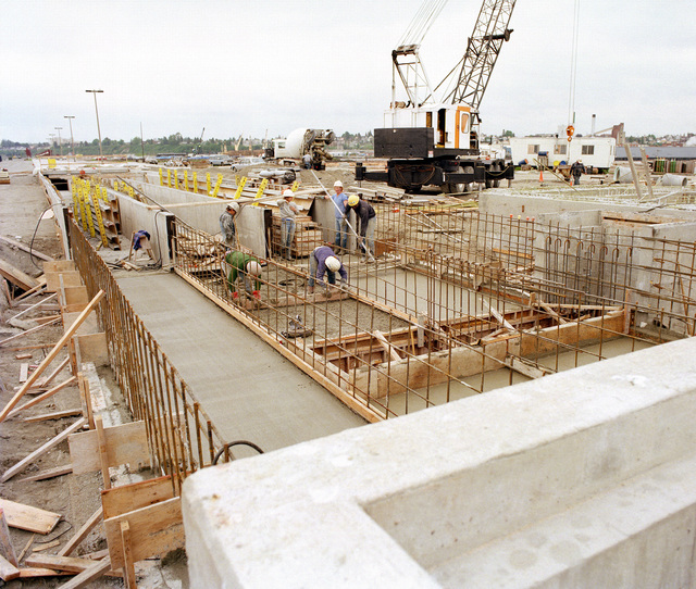 Construction crews smooth concrete during construction of Naval Station Everett, the future home of a carrier battle group
