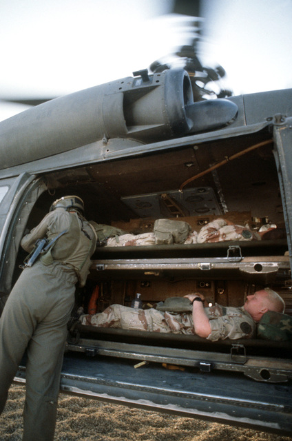 """A crew member from the 57th Medical Detachment, Fort Bragg, N.C., prepares two """"patients"""" for removal from a UH-60 Black Hawk (Blackhawk) ambulance helicopter during an Operation Desert Shield medical training exercise."""