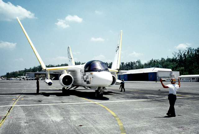 A ground crew member signals to the pilot of a Fleet Logistics Support Squadron 50 (VRC-50) S-3A Viking aircraft as it is positioned on the flight line. The squadron will be relocating to Andersen Air Force Base, Guam, following closure of NAS, Cubi Point and Naval Station, Subic Bay. Control of the instrallations will be assumed by the Subic Bay Metropolitian Authority