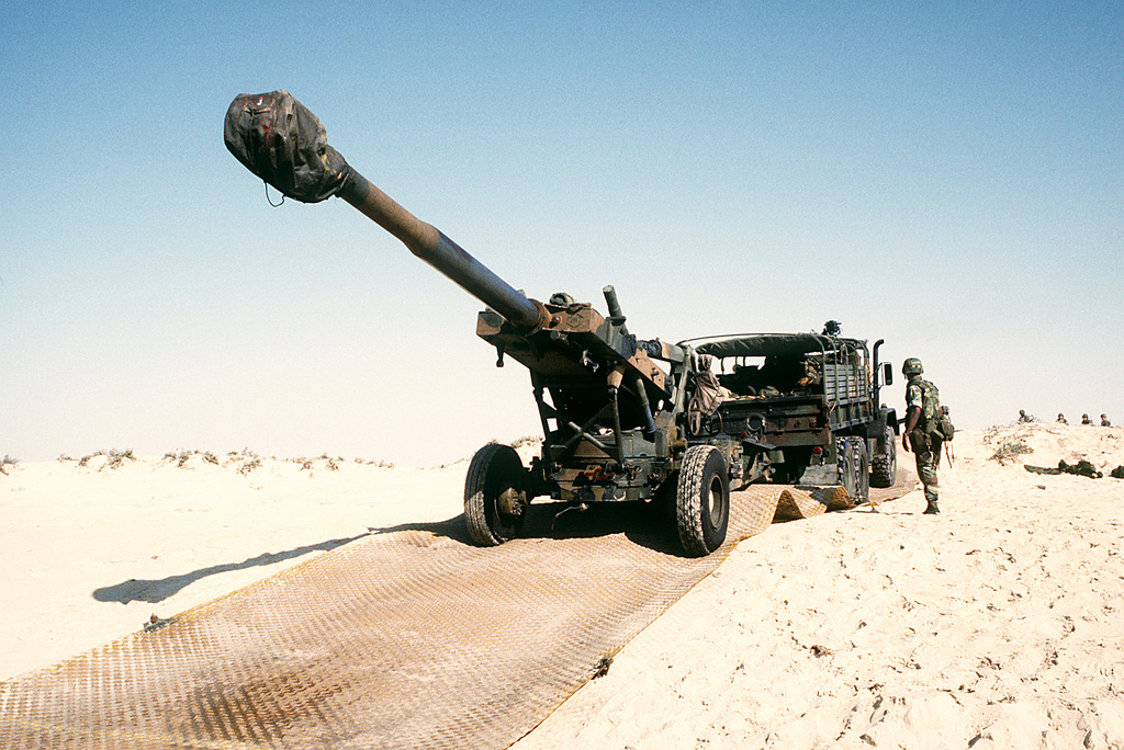 A tactical truck tows an M-198 155mm howitzer from a utility landing craft from the amphibious assault ship USS NASSAU (LHA-4) as Marines from Company A, 2nd Amphibian Assault Vehicle Bn., 4th Marine Expeditionary Brigade, train in an amphibious beach assault exercise in the Persian Gulf during Operation Desert Shield
