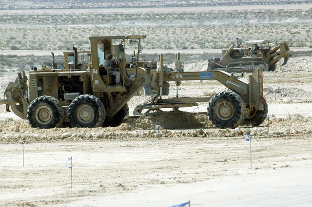 A workman operates a road grader as Army helipads are constructed during Operation Desert Shield