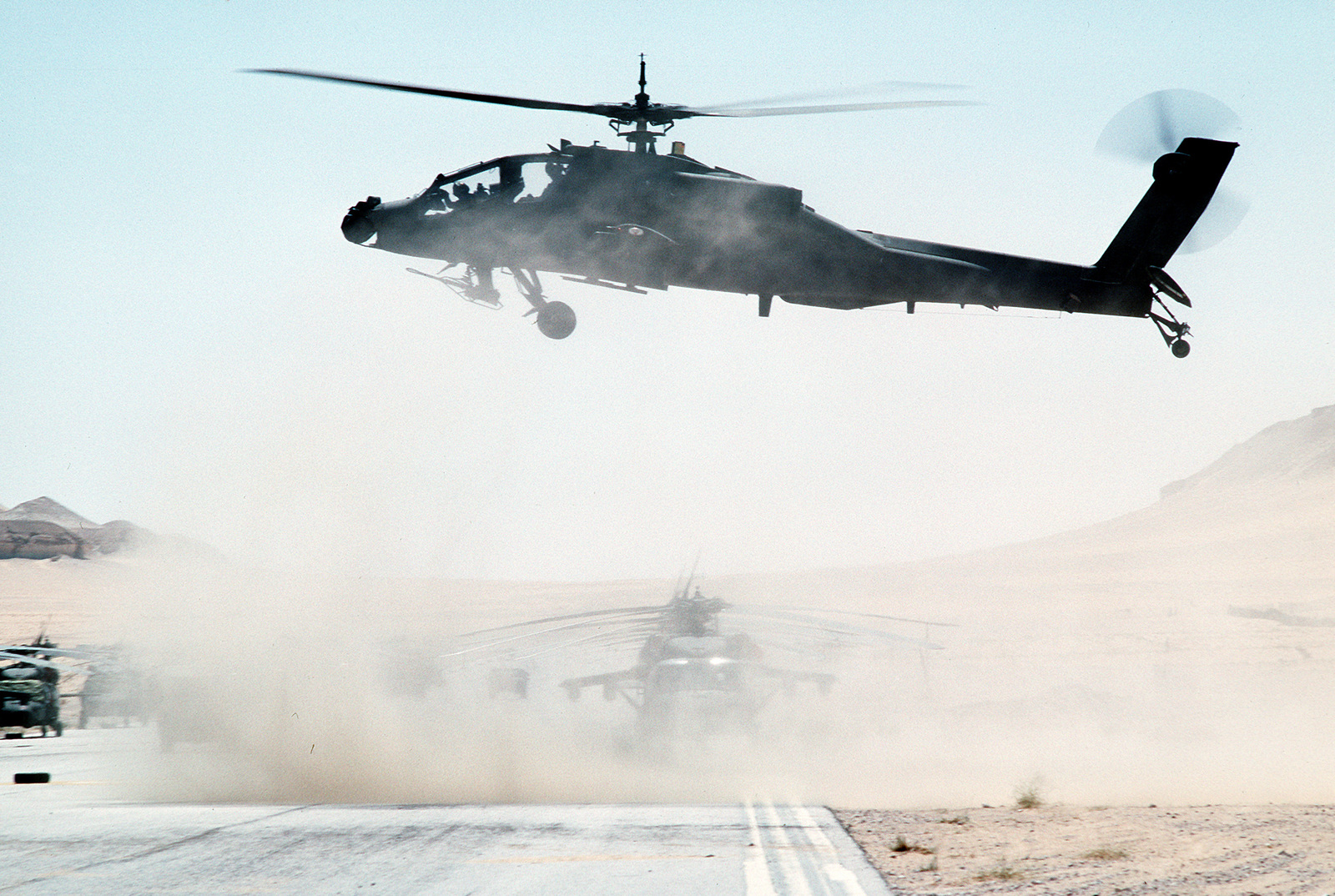 An AH-64 Apache helicopter lifts off as the 82nd Aviation Brigade relocates in the desert during Operation Desert Shield.