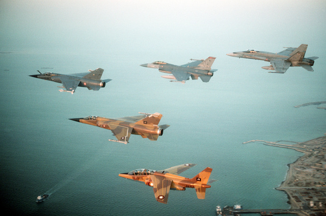 An air-to-air view of a multinational group of fighter jets, including, left to right, a French F-1C Mirage, A Qatari F-1 Mirage, A U.S. Air Force F-16C Fighting Falcon from the 401st Tactical Fighter Wing, a Qatari Alpha Jet, and a Canadian CF/A-18A Hornet, during Operation Desert Shield.