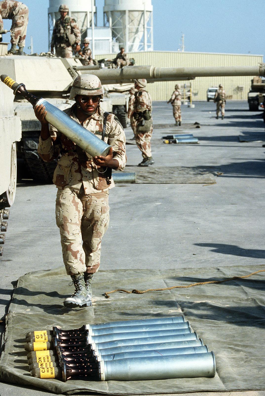 An ammunition specialist carries a 105mm armor-piercing