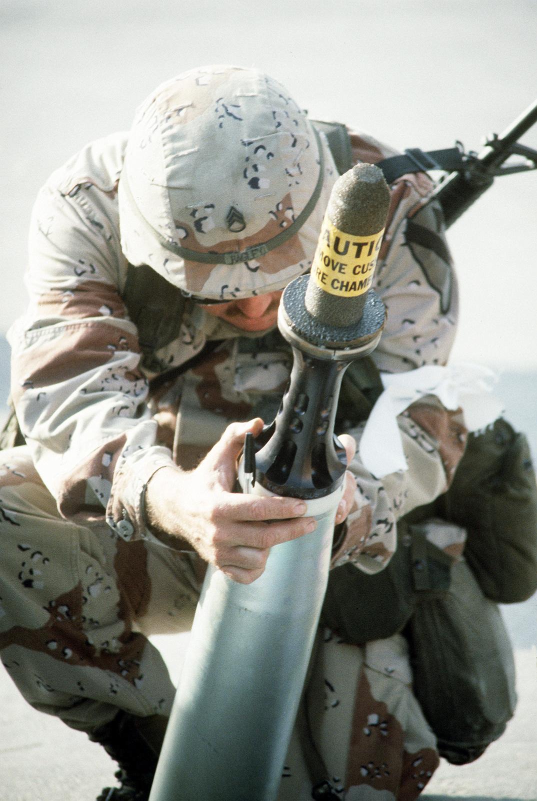 An ammunition specialist examines a 105mm armor-piercing