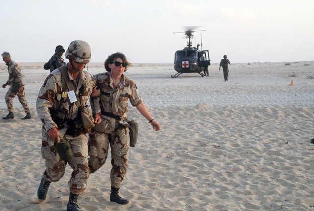 An Army medic, right, assists a soldier to a mobile airlift staging facility for diagnosis and treatment of injuries during Operation Desert Shield. In the background, a UH-60 Black Hawk (Blackhawk) ambulance helicopter waits to takeoff