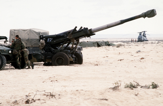 An M-198 155mm howitzer is deployed during an amphibious beach assault exercise by Marines from the 4th Marine Expeditionary Brigade in the Persian Gulf during Operation Desert Shield. In the background, a CH-46E Sea Knight helicopter rests on the beach as the Marines set up camp