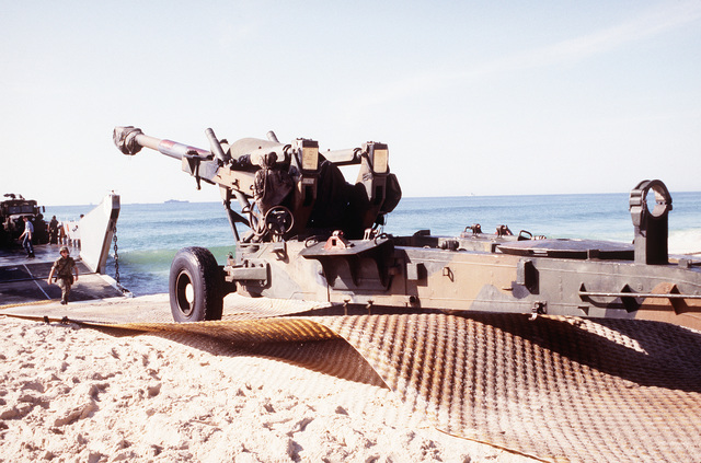 An M-198 155mm howitzer is towed from a utility landing craft from the amphibious assault ship USS NASSAU (LHA-4) on a plastic road mat as Marines from Company A, 2nd Amphibian Assault Vehicle Bn., 4th Marine Expeditionary Brigade, train in an amphibious beach assault exercise in the Persian Gulf during Operation Desert Shield