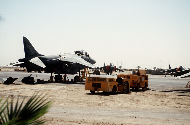 An MD-3A tow tractor and a mobile power plant stand near an AV-8B Harrier aircraft at a Marine guard post during Operation Desert Shield.