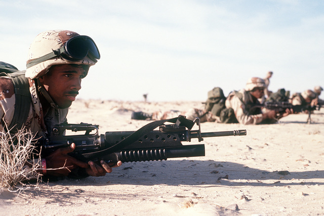 CPL. Ray Penna of Co. C, 1ST Bn., 2nd Marines, guards the camp perimeter with an M-16A2 rifle equipped with an M-203 grenade launcher during an Imminent Thunder training exercise, a part of Operation Desert Shield