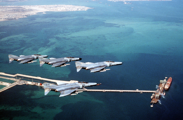 F-4G Phantom fighter aircraft from the 35th Tactical Fighter Wing, Tactical Air Command, foreground, and the 52nd Tactical Fighter Wing, U.S. Air Force Europe, background fly over a pier on the coast of Bahrain during Operation Desert Shield. The aircraft are armed with AGM-88 high-speed, anti-radiation, air-to-surface missiles.
