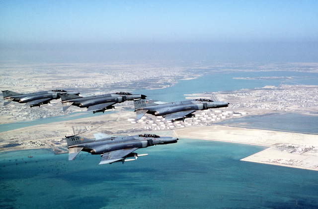 F-4G Phantom fighter aircraft from the 35th Tactical Fighter Wing, Tactical Air Command, foreground, and the 52nd Tactical Fighter Wing, U.S. Air Force Europe, background fly over the coastline of Bahrain during Operation Desert Shield. The aircraft are armed with AGM-88 high-speed, anti-radiation, air-to-surface missiles.