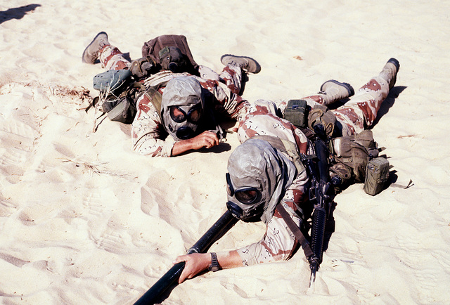 Marines from Co. C, 1ST Bn., 2nd Marines, conduct Bangalore torpedo training while wearing protective masks during Operation Desert Shield