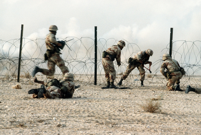 Members of the 1ST Battalion, 325th Airborne Infantry Regiment, make their way through concertina wire during a live fire demonstration for Saudi Arabian national guardsmen. The demonstration is taking place during Operation Desert Shield