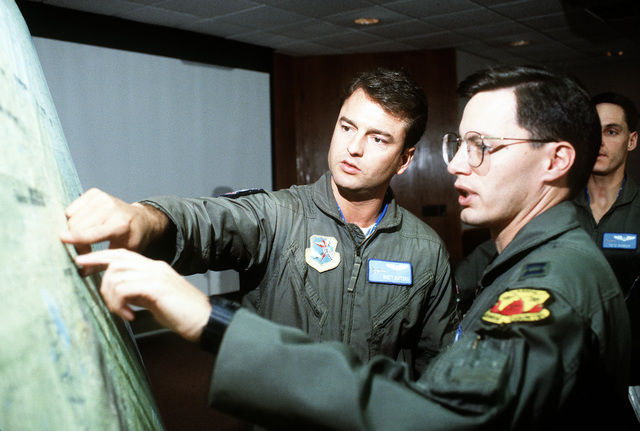 Officers from the 71st Air Refueling Squadron and the 596th Bombardment Squadron consult their planning charts at a joint mission briefing during Proud Shield '92, a Strategic Air Command bombing and navigation competition