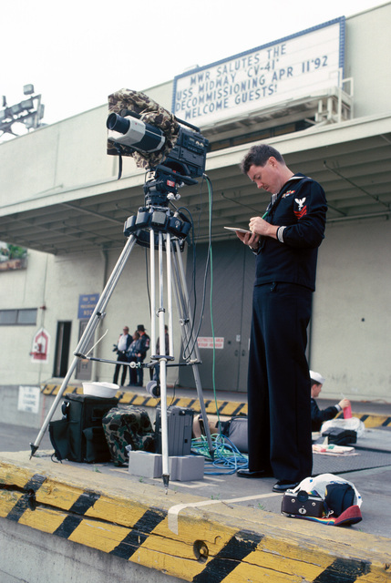 A photographer first class (PH1) is seen making out the shoot sheets which are as necessary as exposing the film. In front of him is a video camera mounted on a tripod to capture the event. He is covering the decommissioning of the aircraft carrier USS MIDWAY (CV-41) which served the nation for forty-seven years
