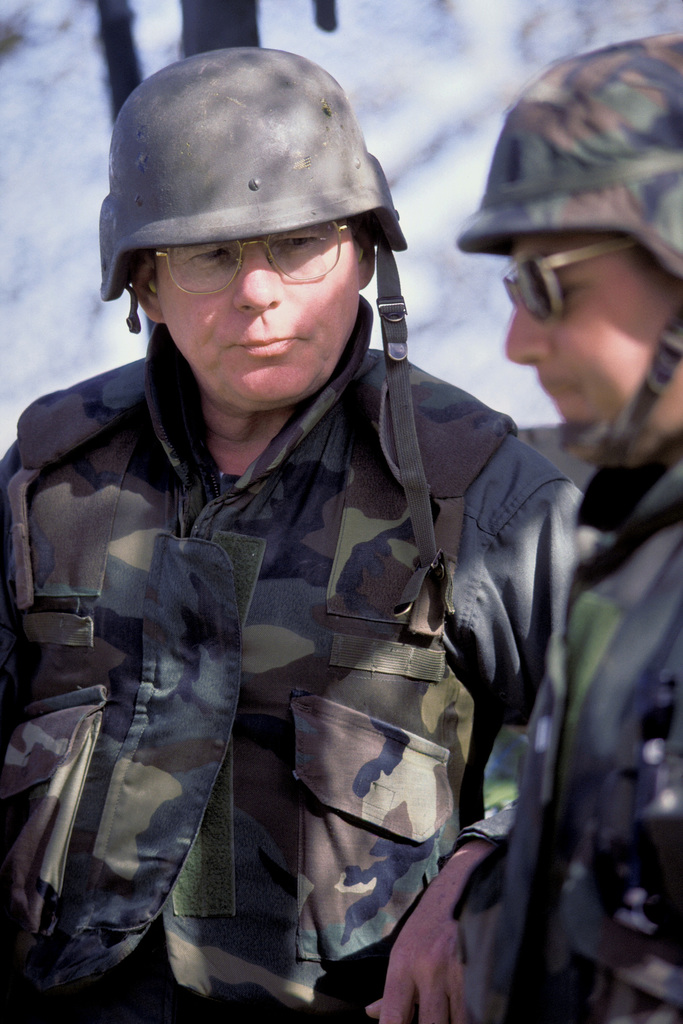 Secretary of the Navy H. Lawrence Garrett wears a helment and flak jacket while observing a demonstration at the Marine Corps Air-Ground Combat Center