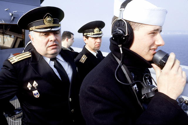 Bulgarian military VIPs observe a U.S. sailor use a sound-powered telephone on the deck of the dock landing ship USS WHIDBEY ISLAND (LSD-41) during a ship tour. The WHIDBEY ISLAND is the first U.S. ship ever to have visited Burgas