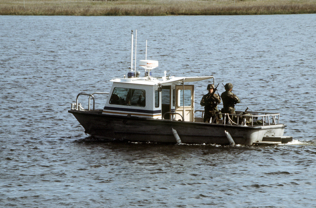Marines of the Security Force Company stand guard with M-16A2 assault rifles while patrolling in a boat near the special weapons area of the submarine base
