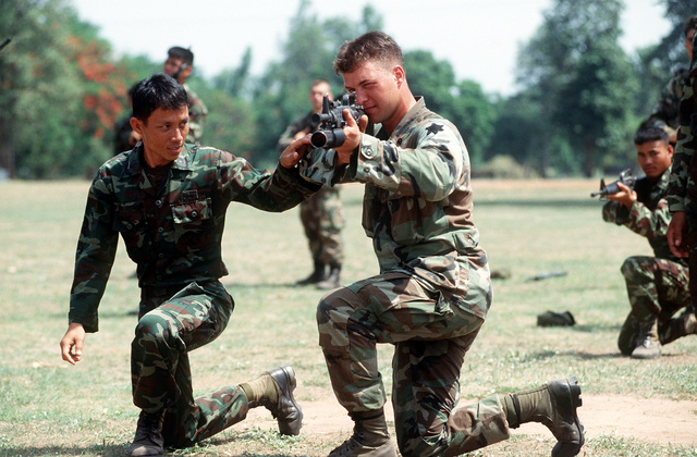 A Thai soldier instructs SPC. Steven Leffelman, a member of the 1ST Battalion, 17th Regiment, 6th Infantry Division, during a quick fire exercise at Camp Friendship during the joint Thai-U.S. training exercise Cobra Gold '92