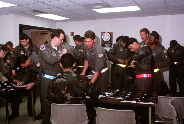 Aircrew members of the 62nd Airlift Squadron, 314th Airlift Wing, are issued pistols while preparing for an airdrop mission as part of an operational readiness inspection (ORI) and exercise Ocean Venture '92