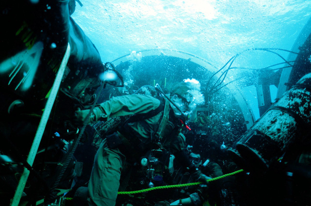Members of the Navy Sea-Air-Land (SEAL) team emerge from a dry deck shelter aboard the submerged nuclear-powered attack submarine USS SILVERSIDES (SSN-679). Members are taking part in lock-out procedures off the coast of Key West, Fla., during exercise Phantom Striker