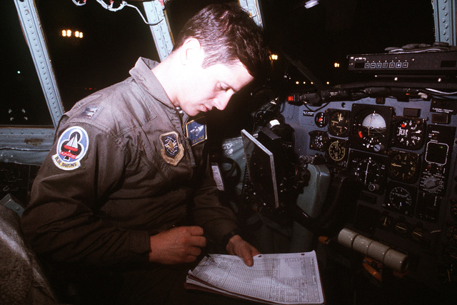 Pilot CAPT. Gene Maples sits in the cockpit of a 62nd Airlift Squadron C-130 Hercules aircraft as he reviews a preflight check list prior to an airdrop mission as part of an operational readiness inspection (ORI) and exercise Ocean Venture '92